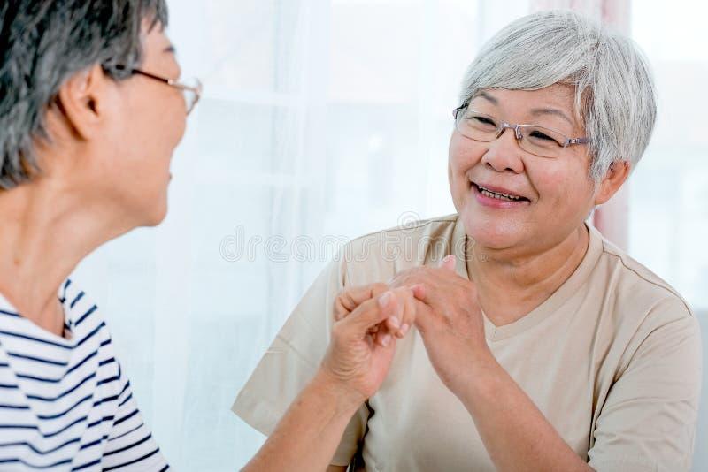 一个亚洲年长妇女勾子每其他对其他的小指与微笑在阳台前面在房子里 免版税图库摄影