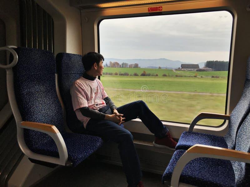一个亚裔人乘从萨尔茨堡到Hallstatt,奥地利的火车 免版税库存图片