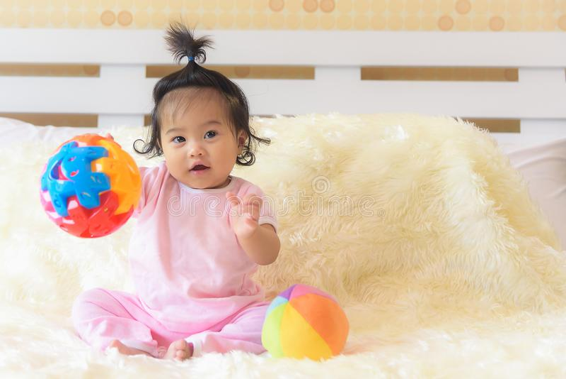 一个亚裔女婴充当她的与一个愉快的表示的床 图库摄影