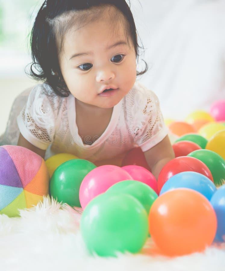 一个亚裔女婴充当她的与一个愉快的表示的床 库存图片