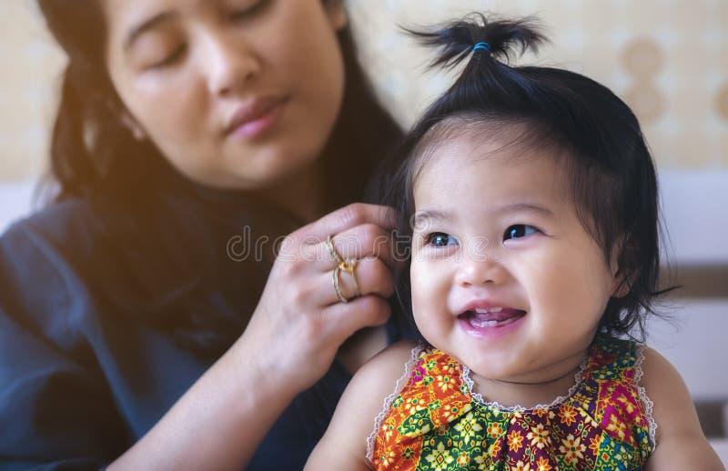 一个亚裔婴孩充当她的与她的母亲的床后面的, 库存照片