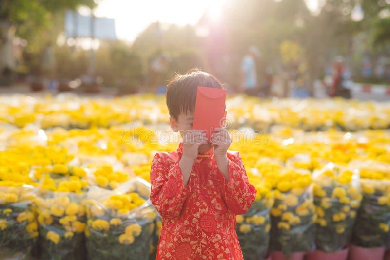 一个亚裔男孩的画象传统节日服装的 ao戴礼服微笑的逗人喜爱的矮小的越南男孩 Tet假日 月球 库存图片