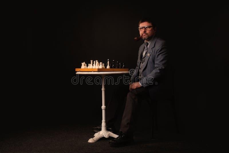 一个人下棋并且抽在黑暗的背景的一个管子 图库摄影