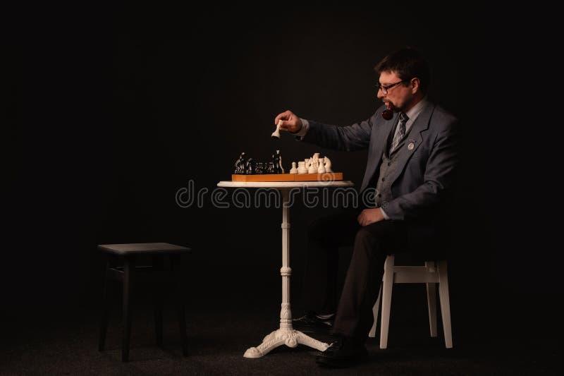 一个人下棋并且抽在黑暗的背景的一个管子 免版税库存图片