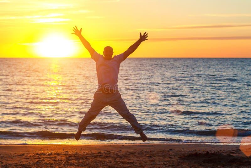 一个人享有在海滩的生活在日落 免版税图库摄影