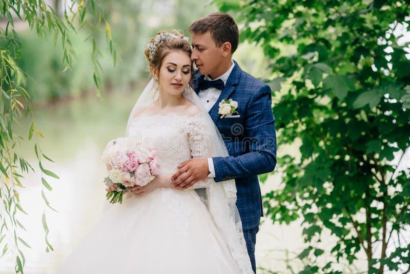 一个人从后面拥抱心爱的他的 女孩盖她的眼睛,她感到愉快和镇静在婚礼之日 摆在年轻人 免版税库存图片