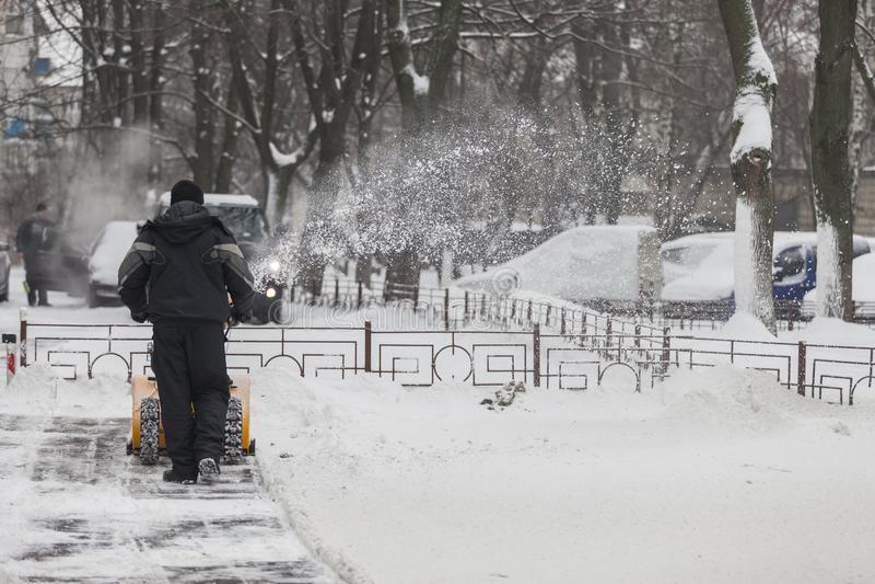 一个人从边路清洗雪与吹雪机 库存图片