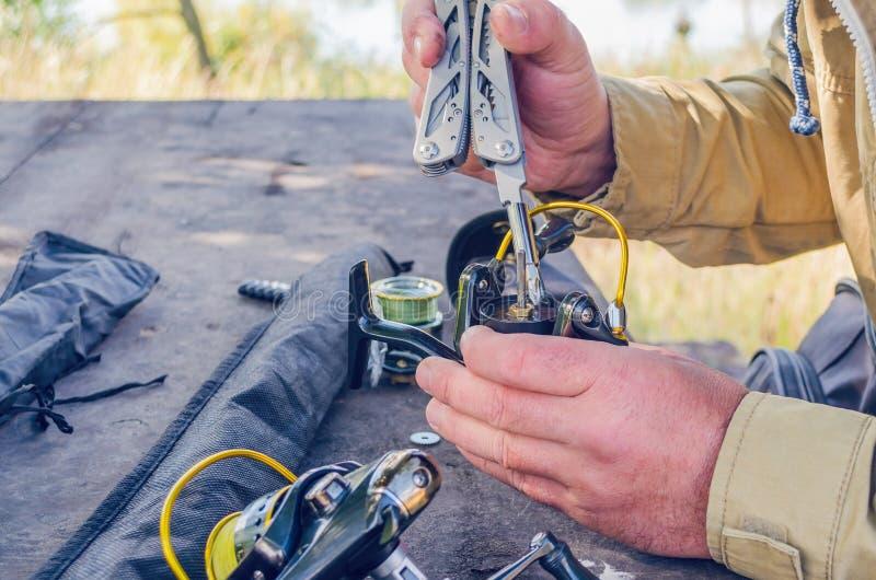一个人修理与被即兴创作的手段的一个钓鱼的卷轴 免版税库存图片