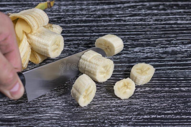 一个人切开一把香蕉刀子成在一张老黑木桌上的切片 免版税图库摄影