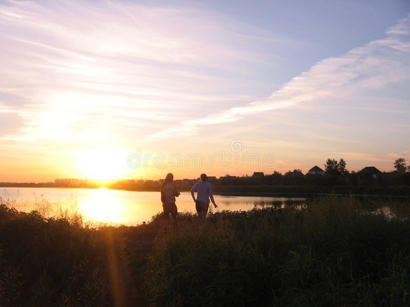 一个人和一个女孩的剪影湖的落日的光芒的 免版税图库摄影