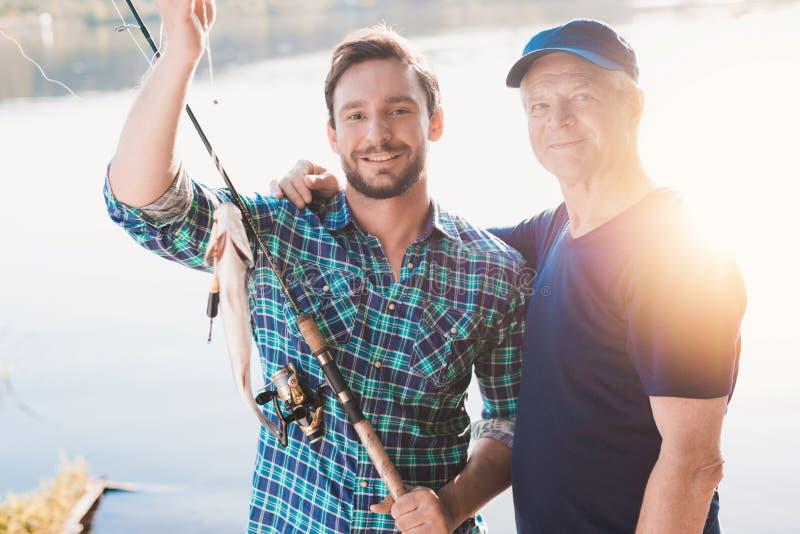 一个人和一个老人摆在与一个人抓的鱼 在他们后,太阳在河被反射 库存图片