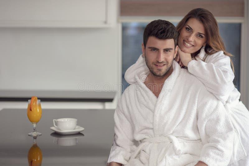 一个人和他的妻子的画象在厨房里,当食用早餐时 库存照片