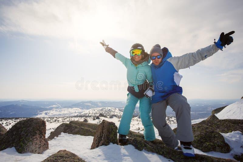 一个人和女孩挡雪板在山顶部与Th 库存图片