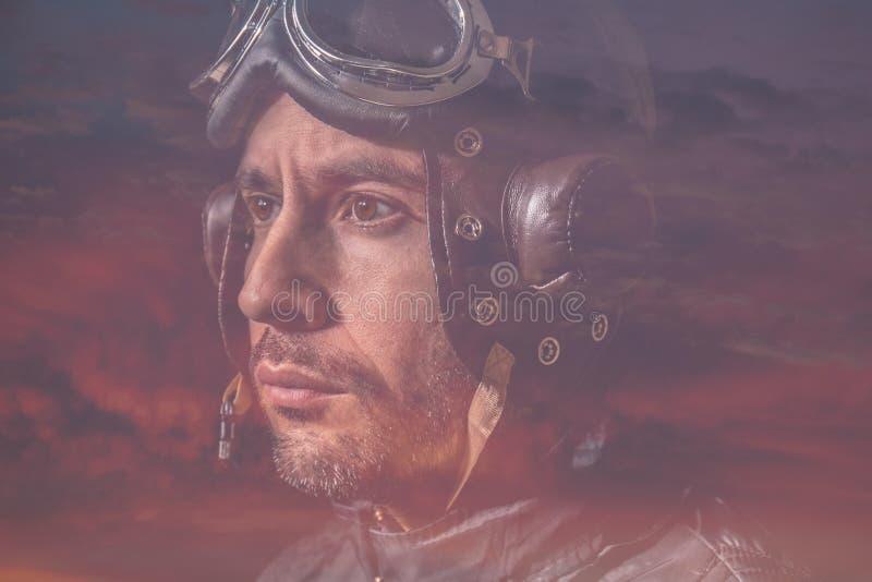一个人和风镜的画象的两次曝光注视着入距离和云彩的有飞行员盔甲的日落 免版税库存照片