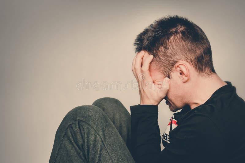 一个人哭泣 消沉的年轻人坐握手的地板 人掩藏他的面孔用他的手 头疼 掩藏 库存照片