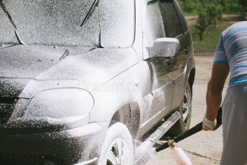 一个人喷洒洗涤在汽车的洗涤剂高压 免版税库存照片