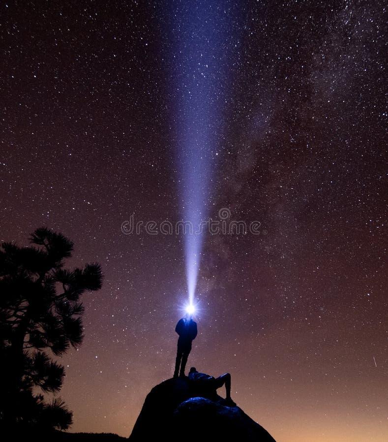一个人在与前灯的一个岩石站立,当另一休息时 库存图片