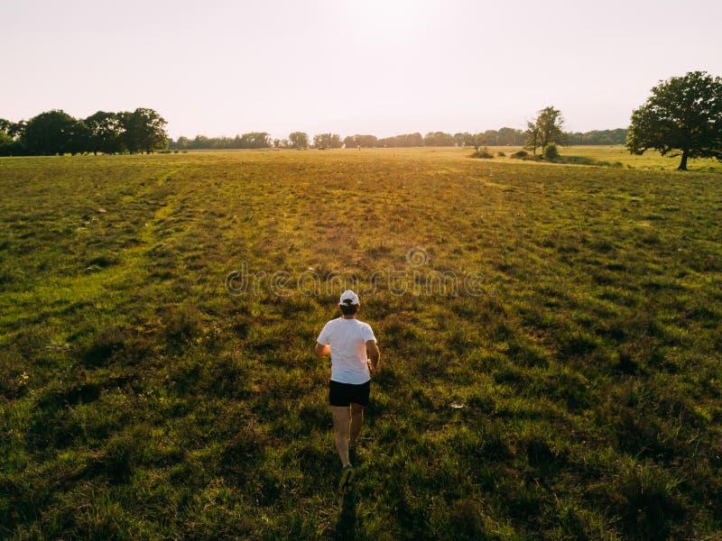 一个人在乡下跑在日落 免版税库存照片