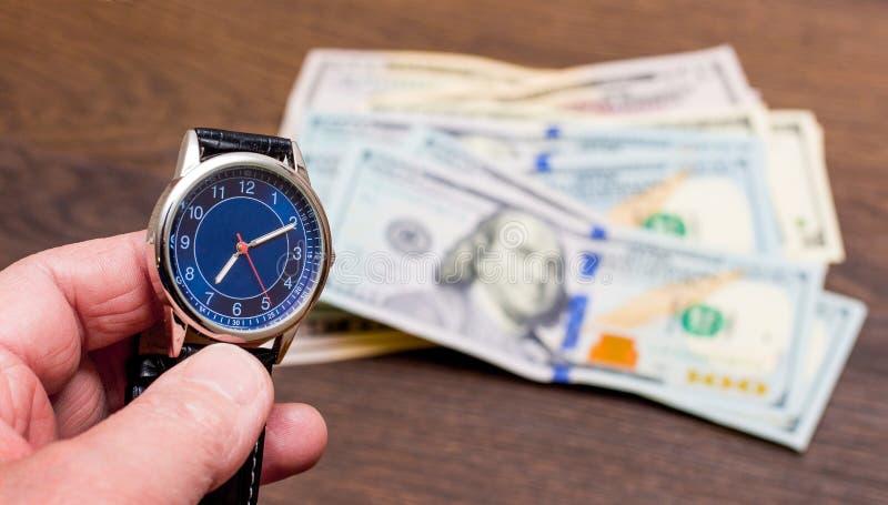 一个人在他的手上拿着一个时钟反对美金 时刻挣钱 时间是货币 拷贝space_ 免版税库存图片