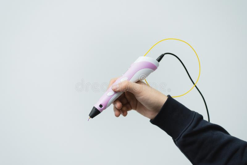 一个人在他的手上拿着一支3d笔 3d笔在一个人的手上 画的技术塑料把柄 免版税库存图片