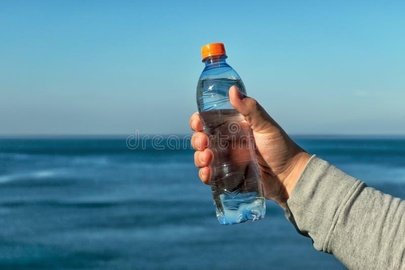 一个人在他的手上拿着塑料瓶饮用水,站立在海洋 库存照片