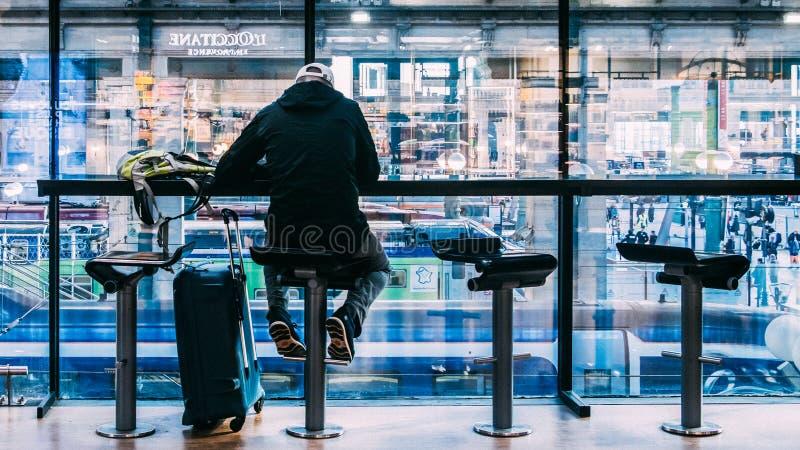 一个人在他的行李旁边坐在下面咖啡馆俯视的乘客和火车在巴黎的Gare du诺德驻地 免版税库存图片