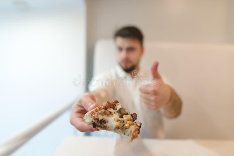 一个人在入口在他的手上拿着比萨饼并且显示他的手指 一个人喜欢薄饼 象 免版税图库摄影