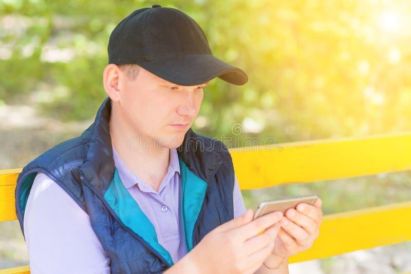 一个人在公园坐并且调查电话 库存照片