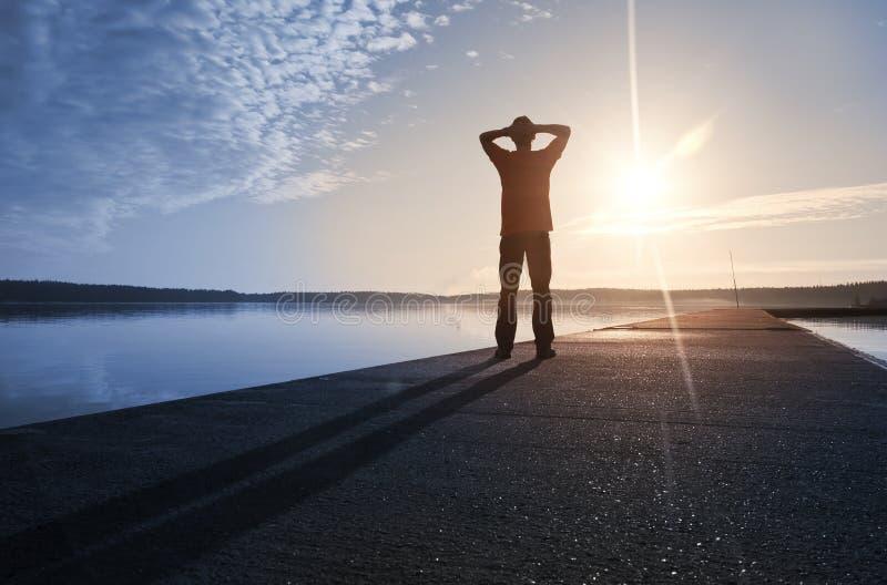 一个人在具体码头在阳光下突出 免版税库存照片