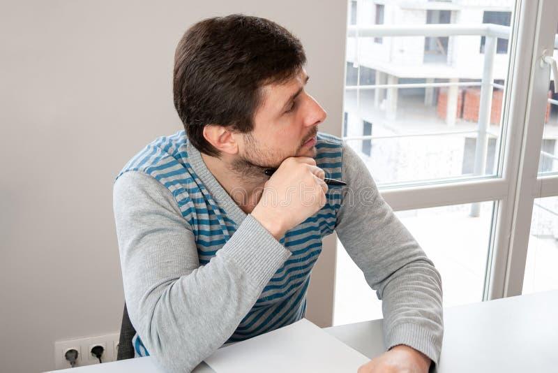 一个人在办公室坐在与一支笔的一张桌上在他的手和一张空白的纸片上并且听殷勤地 库存照片