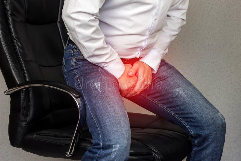 一个人在办公室椅子坐并且坚持鼠蹊,裤裆,前列腺炎,平均计划 库存照片