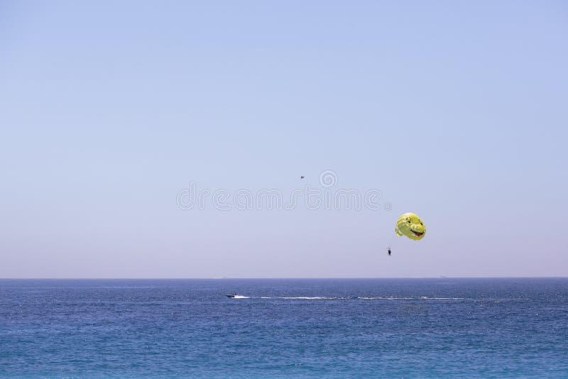 一个人在小船的一个降伞飞行 帆伞运动 库存照片
