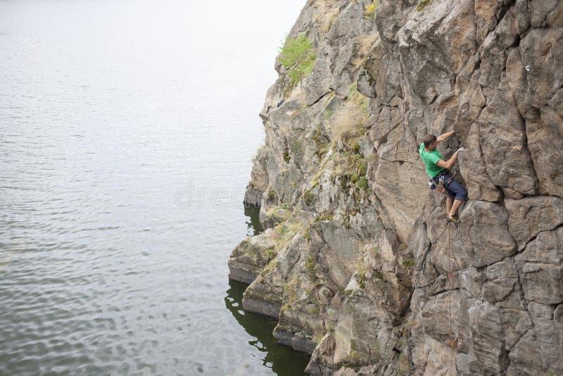一个人在岩石上升在水附近 免版税库存照片