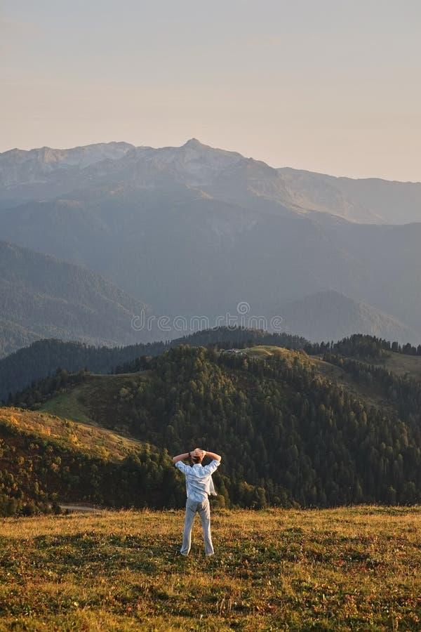 一个人在峭壁的峰顶站立与他的回到照相机,享受绿色森林和美丽的mou的一个风景看法 库存图片