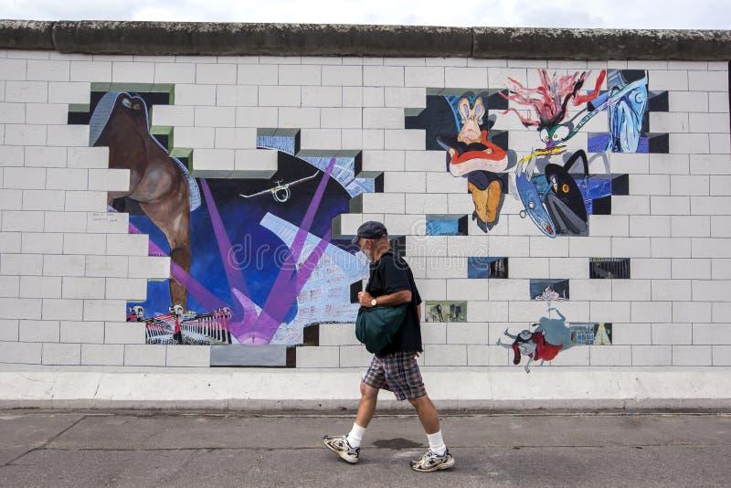一个人在德国走报道前臭名昭著的柏林围墙的部分的一张五颜六色的壁画 免版税库存图片