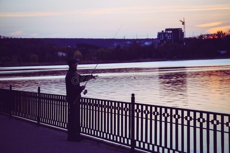 一个人在晚上钓鱼在湖 免版税库存图片