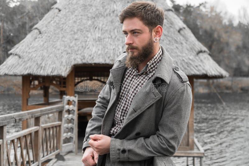 一个人在河的河岸站立 英俊的人公园 在自然的秋天步行 免版税库存图片