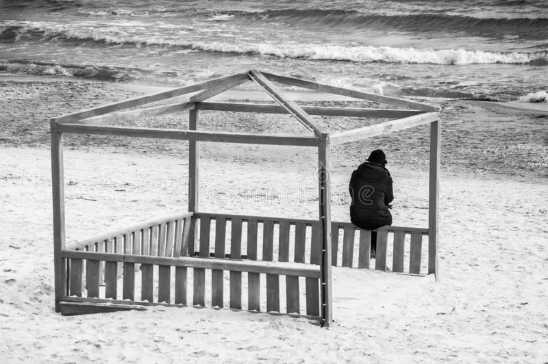 一个人在海前面坐 ?? 免版税库存照片
