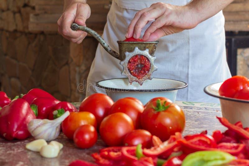 一个人在肉磨机里磨番茄和保加利亚胡椒制作菜 库存照片