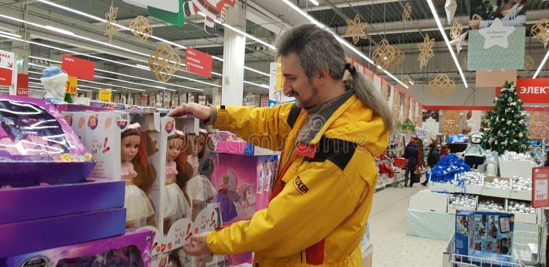 一个人在超级市场选择孩子的礼物玩具,玩偶的部门的 免版税库存图片