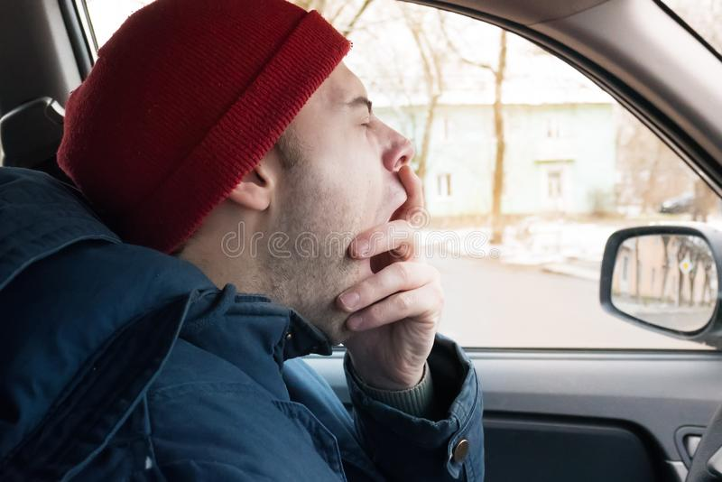 一个人在路乘坐在冬天,在轮子的一个人哈欠,疲倦于驾驶 免版税库存图片