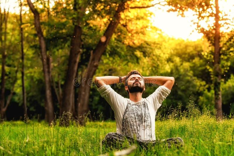 一个人坐草在公园和舒展 免版税库存照片