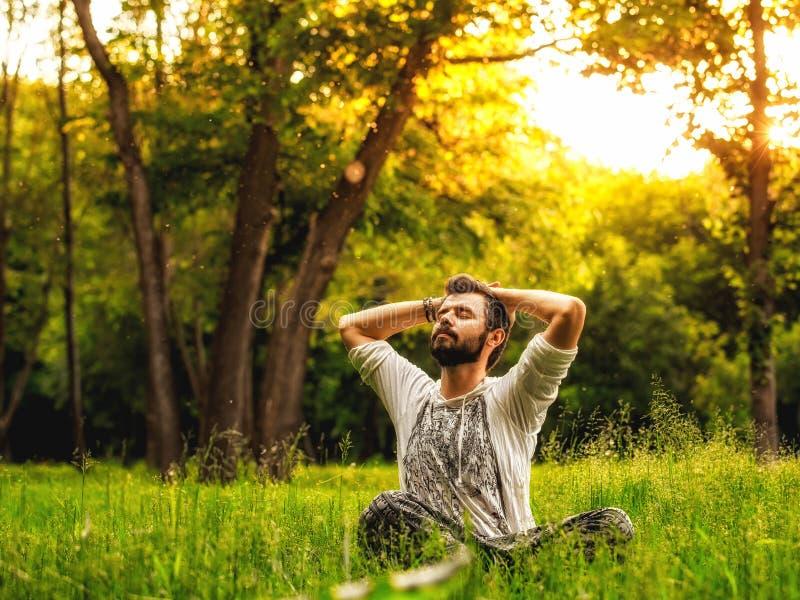 一个人坐草在公园和舒展 库存图片