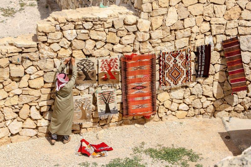 一个人垂悬五颜六色的地毯待售,约旦 免版税库存图片