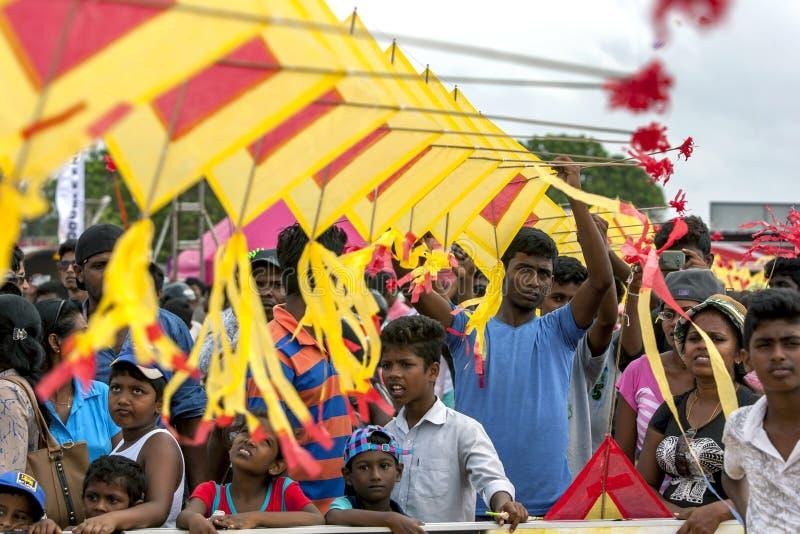 一个人帮助拿着在人上人群的日本风筝Negombo的在斯里兰卡靠岸 免版税图库摄影