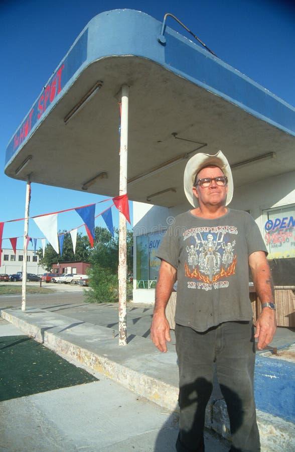 一个人常设在一个被放弃的加油站之外 免版税图库摄影