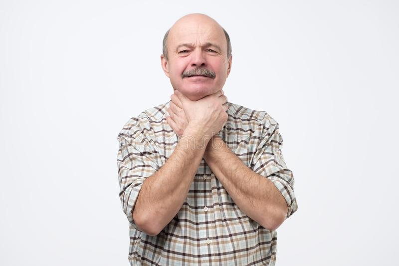 一个人强烈地劫掠他的喉头用两个手和半眯着的眼睛从痛苦在他的喉头 库存图片