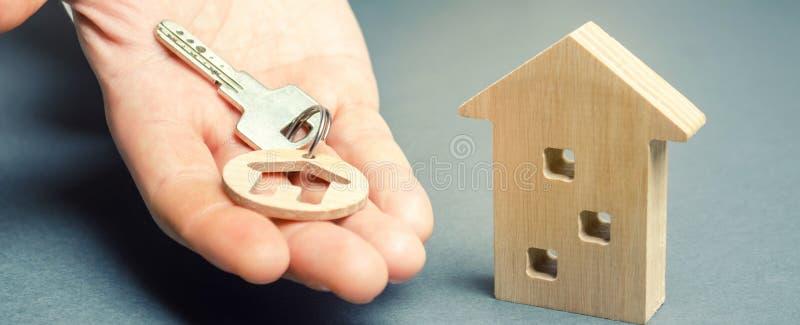 一个人把握与房子和一个木家的一个小装饰品关键 r 地产商服务 ( 购买住房 免版税库存照片