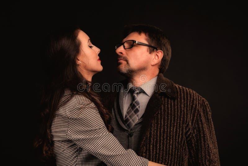一个人拥抱一个女孩反对黑暗的背景 免版税图库摄影