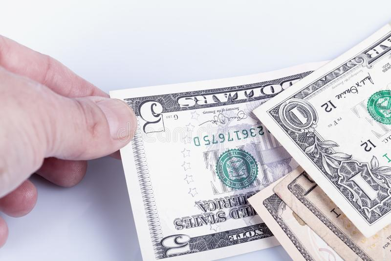 一个人拾起五美元票据从在堆之间和隔绝在白色 图库摄影